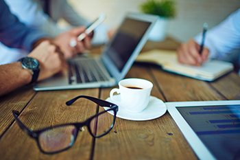 Cup of coffee and eyeglasses in working environment