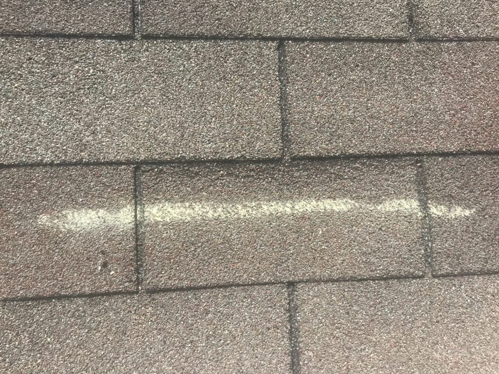Wind damaged roofing shingle marked by inspector