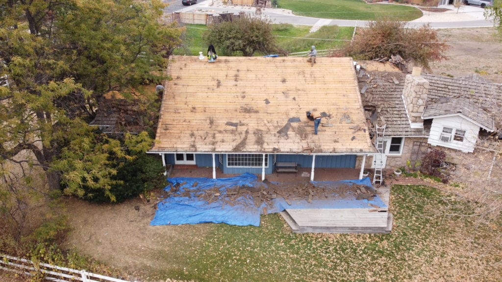 Image shows old shake roof removed and preparations for a new metal roof